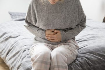 Sick woman in grey homewear sitting on bed, keeping hands on stomach, suffering from intense pain. Illness, stomach ache concept